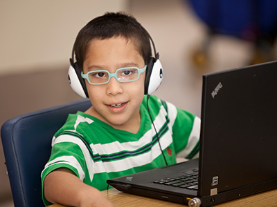Child in-front of laptop with headphones